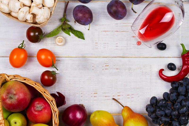 Mushrooms, grape, plums, onion, tomatoes, chilli peppers, glass of red wine, apples and pears in basket. View from above royalty free stock photography