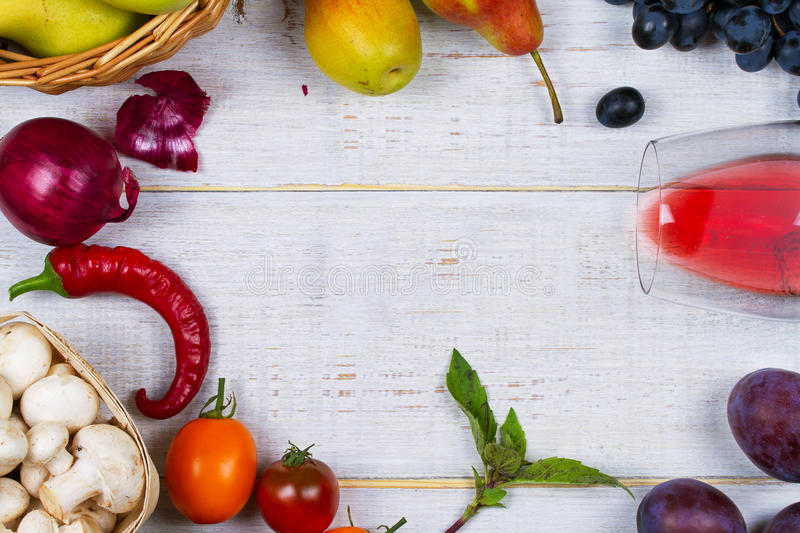 Mushrooms, grape, plums, onion, tomatoes, chilli peppers, glass of red wine, apples and pears in basket. View from above royalty free stock images