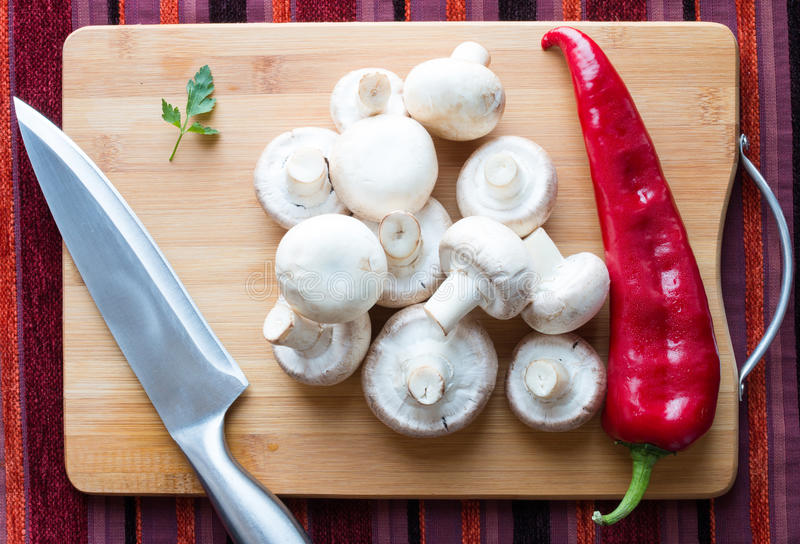 Mushrooms, parsley and bell pepper. Fresh mushrooms, parsley and bell pepper on wooden cutting board with kitchen knife royalty free stock image