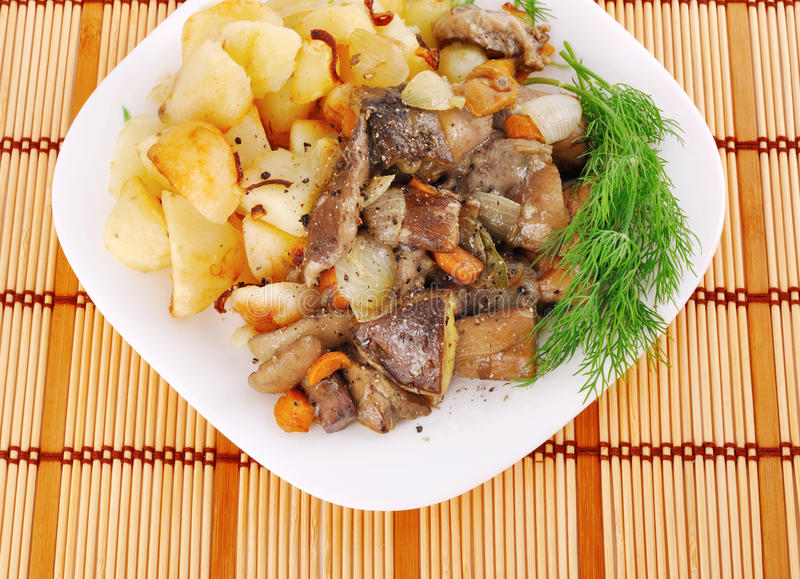 Mushrooms with potatoe2. Mushrooms with potatoes in a rural, on a plate, with greens stock photos