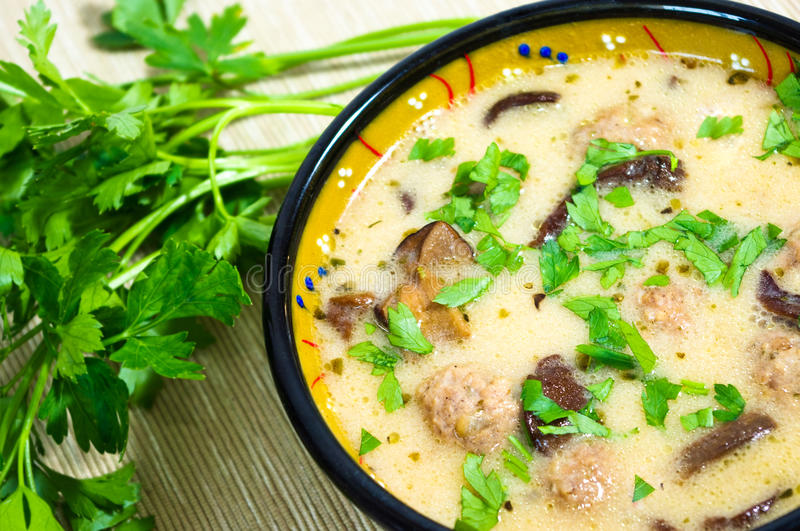 Mushrooms soup. With meatballs and parsley stock images