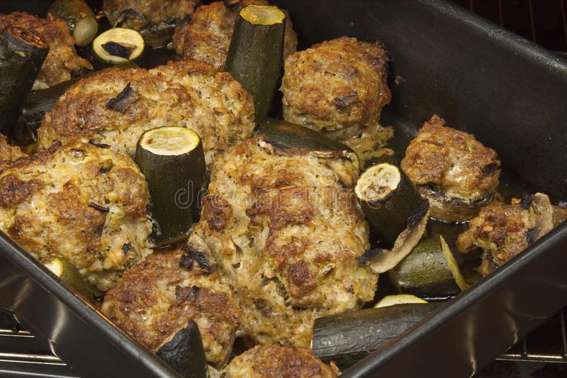 Mushrooms stuffed with minced meat with zucchini. Roast on a roasting pan in the oven royalty free stock image