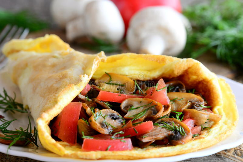 Mushrooms, tomatoes omelette breakfast. Omelette stuffed with mushrooms, tomatoes and dill on a plate and old wooden background royalty free stock photography