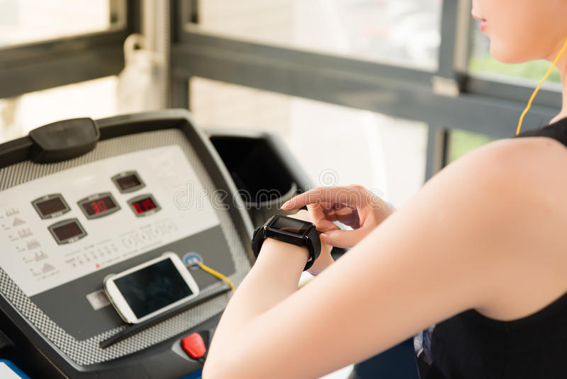 Musi de écoute asiatique de fréquence du pouls de contrôle de smartwatch d'utilisation de femme de sport image libre de droits