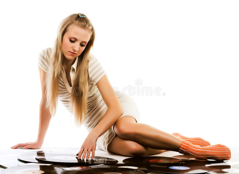 Music. Blond girl laying on white with vinyl records stock photography