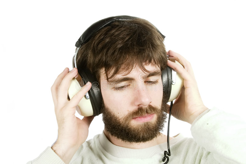 Music. A young male with a beard listening to music on large retro headphones. Isolated on white with clipping path stock photo