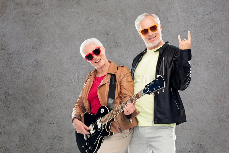 Senior couple with guitar showing rock hand sign. Music, age and people concept - happy senior couple in sunglasses with electric guitar showing rock hand sign royalty free stock photo