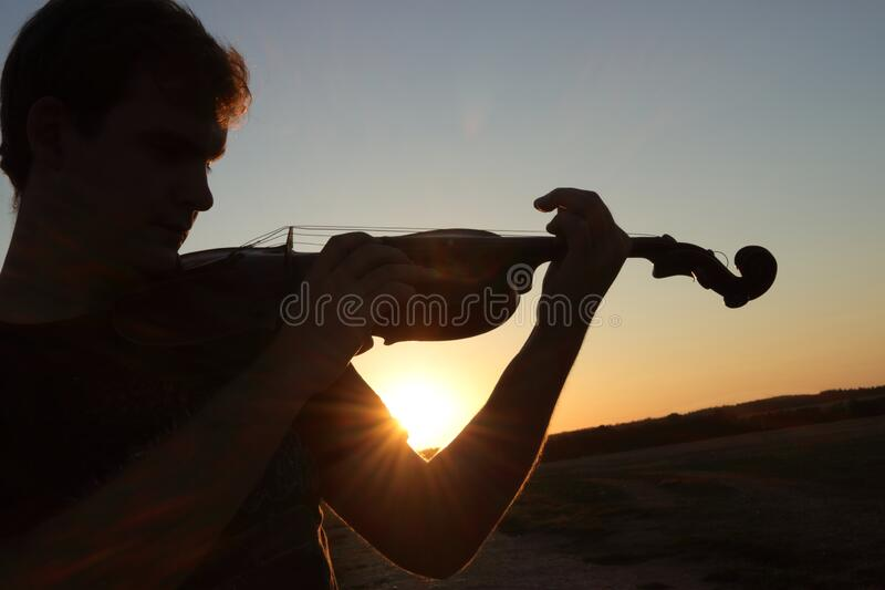 Music arrange of silhouette of man playing the violin at sunset, sunrise. Player, instrument and skyline is black and light sun. And blue sky is on background royalty free stock photos