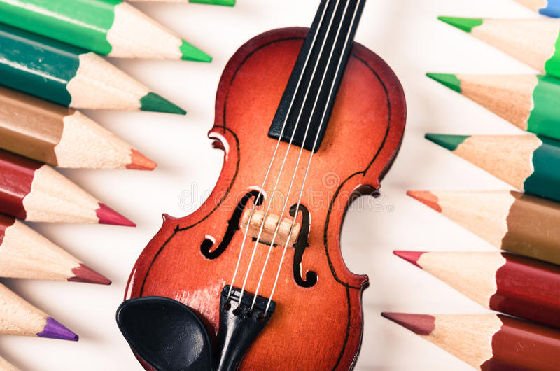 Music and art concept. Violin and color pencil on white background. Music and art concept stock photos