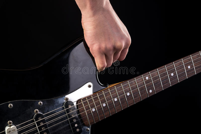 Music and art. Electric guitar in hand, on a black isolated background. Horizontal frame. Music and art. Electric guitar in hand, on a black isolated background stock photography