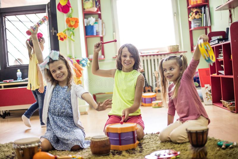 Music awakens creativity in them. Children in preschool stock photos