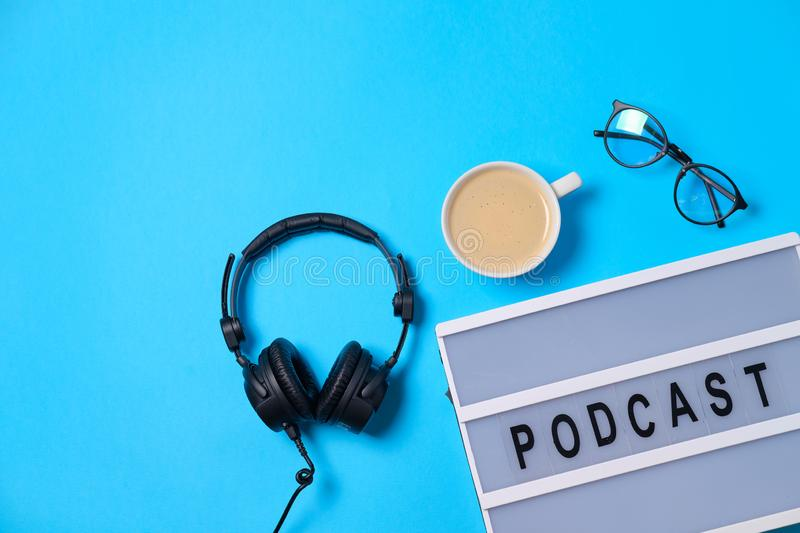 Music  background with Podcast word on lightbox,  headphones and cup of coffee on blue table, flat lay. Top view, flat lay, space. For text royalty free stock photos