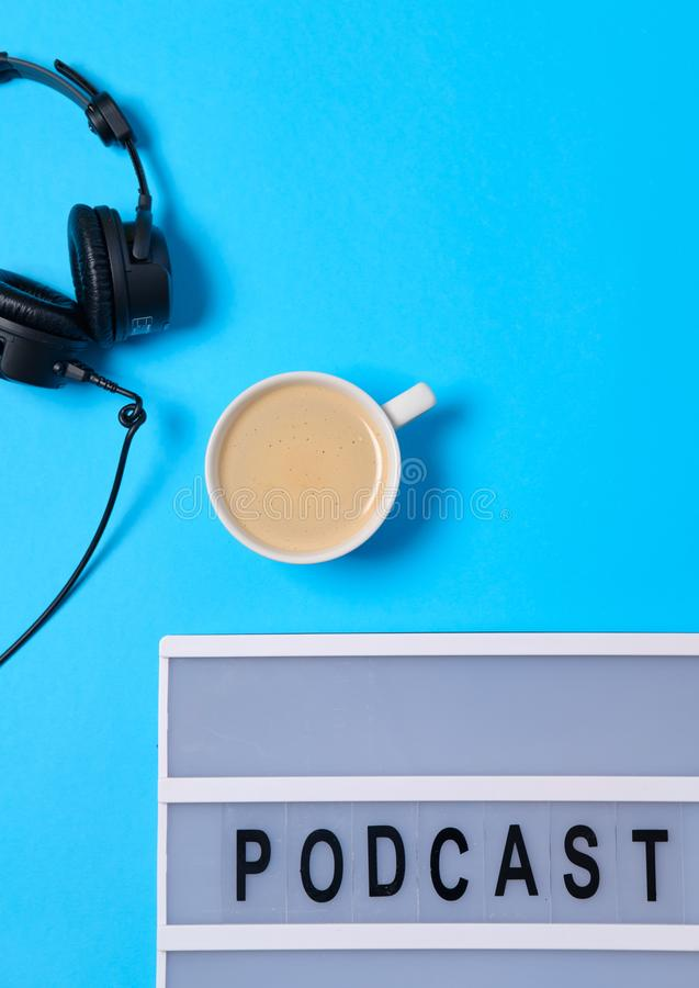 Music  background with Podcast word on lightbox,  headphones and cup of coffee on blue table, flat lay. Top view, flat lay, space stock photography