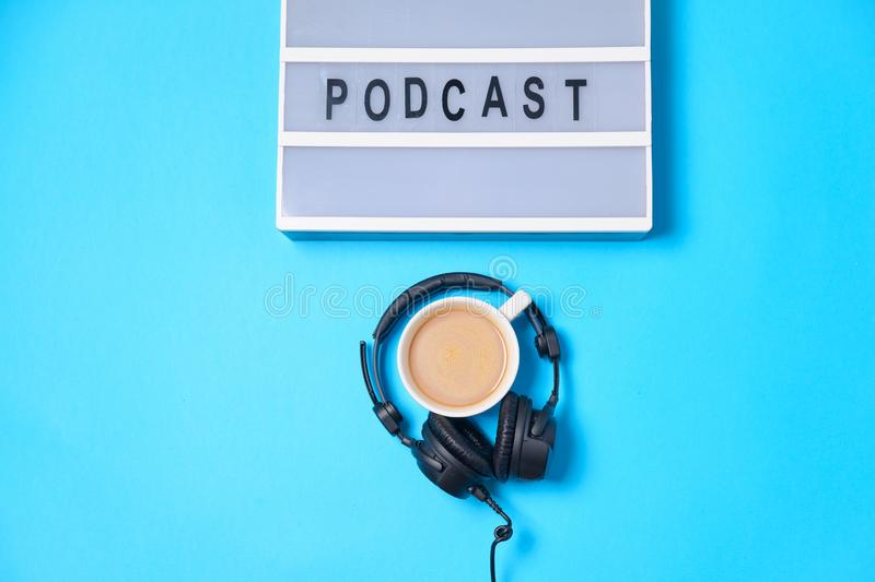 Music  background with Podcast word on lightbox,  headphones and cup of coffee on blue table, flat lay. Top view, flat lay, space. For text stock image