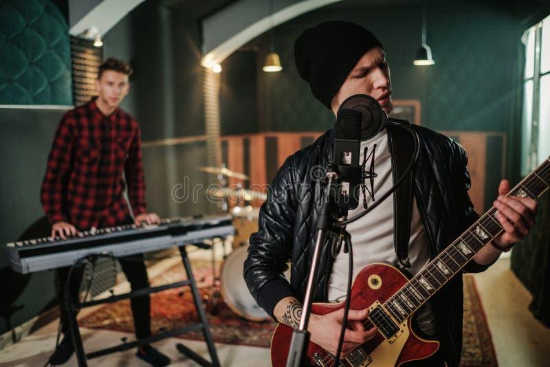 Music band having rehearsal in a studio.  stock photos