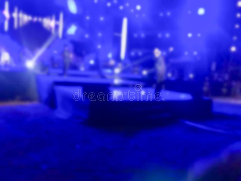 Music band perform on a concert stage with color light shining. Singer hold microphone and walk on stage royalty free stock image