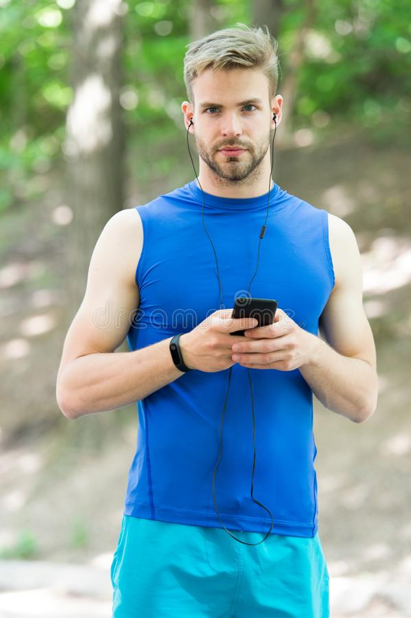 Music best companion to run. Man athlete on busy face set up play list, nature background. Sportsman training headphones stock photography