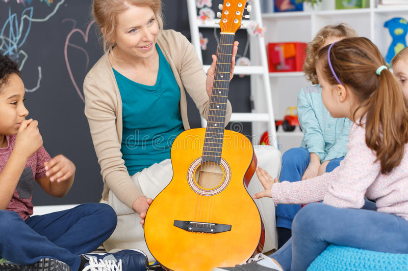 Music classes for kids. Kindergarten teacher during music classes with guitar for kids royalty free stock photo