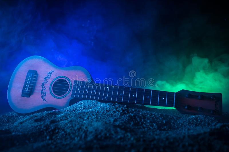 Music concept. Acoustic guitar isolated on a dark background under beam of light with smoke with copy space. Guitar Strings, close royalty free stock photos