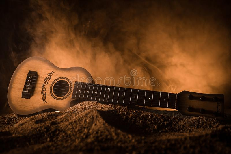 Music concept. Acoustic guitar isolated on a dark background under beam of light with smoke with copy space. Guitar Strings, close royalty free stock image