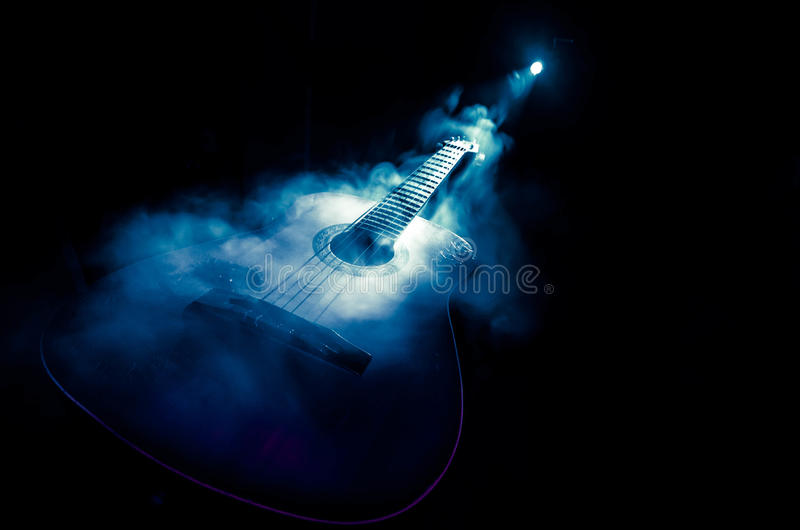 Music concept. Acoustic guitar isolated on a dark background under beam of light with smoke with copy space. Guitar Strings, close stock image