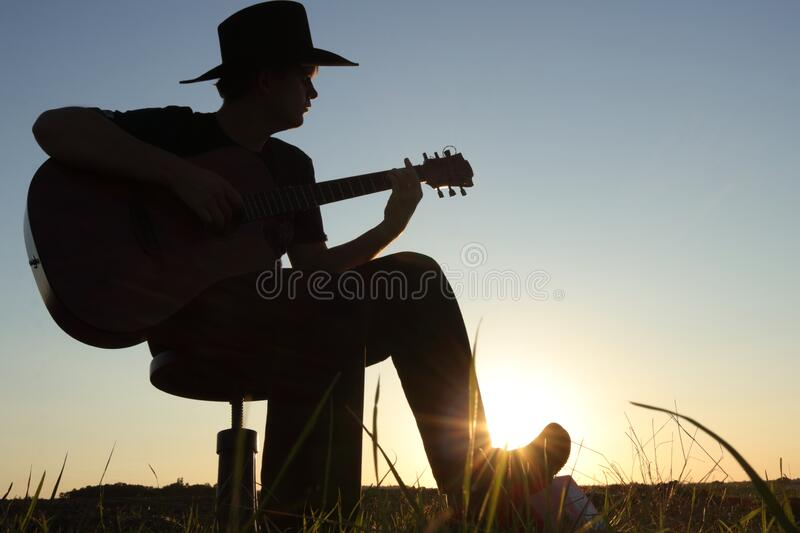 Music concept of black silhouette of man with western hat cowboy and instrument at sunset or sunrise with skyline and grass. Musician playing guitar outside in royalty free stock photos