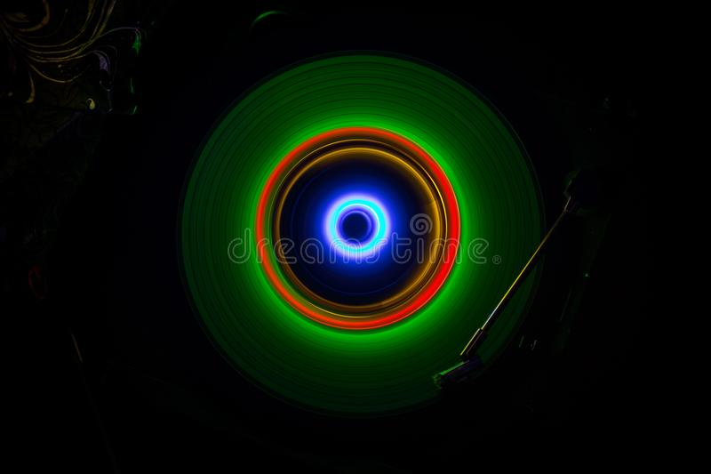 Music concept. Freezelight glowing vinyl on dark background or Turntable playing vinyl with glowing abstract lines concept on dark. Background. For Club poster stock photo