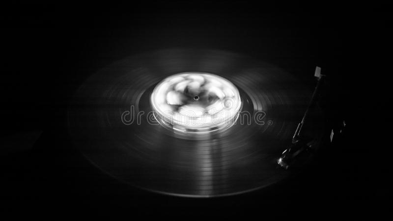 Turntable playing vinyl with glowing abstract lines concept on dark background. Music concept. Freezelight glowing vinyl on dark background or Turntable playing royalty free stock photo