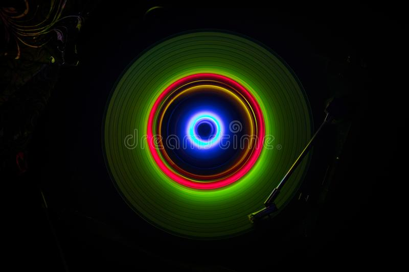 Music concept. Freezelight glowing vinyl on dark background or Turntable playing vinyl with glowing abstract lines concept on dark. Background. For Club poster stock images