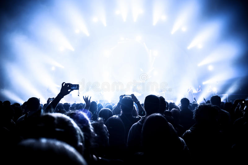 Music concert. Many people enjoying evening in night club, live sound, musicians on the stage, popular band, fun and joy concept, New Year celebration stock photo