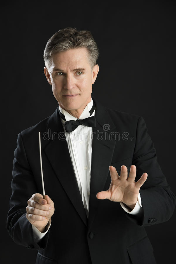 Download Music Conductor Gesturing While Directing With His Baton Stock Photo - Image of leadership, event: 32062206