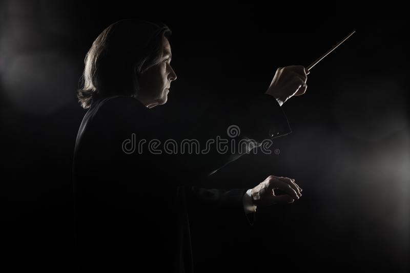 Music conductor woman conducting the orchestra. Conductor with baton. Maestro with stick Symphony concert stock images