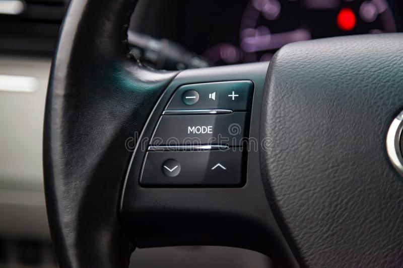 Music control buttons via bluetooth on the steering wheel of the car close-up, royalty free stock photo