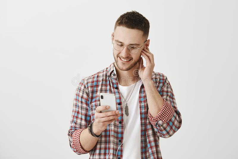 Music describe feelings. Studio shot of attractive caucasian guy in glasses looking at screen of smartphone, picking royalty free stock photography