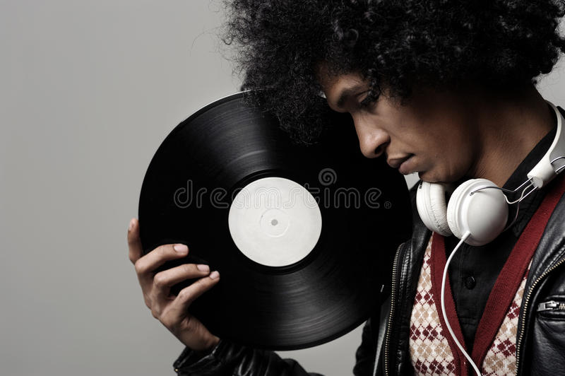 Music DJ portrait. Retro dj portrait in fashion style isolated on grey background in studio. Modern music man with afro hairstyle, headphones and vinyl record royalty free stock photo