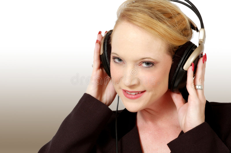 Music Downloads. Beautiful woman with electronic head sets for listening to music. Gradient background royalty free stock photography