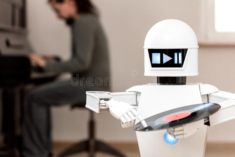Music entertainment service robot is playing music. Files while a man in the background is playing a piano royalty free stock images