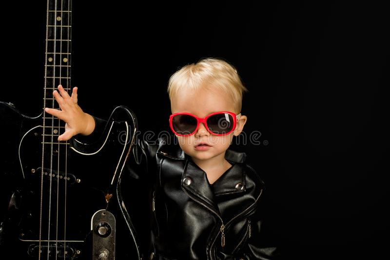 Music for everyone. Adorable small music fan. Small musician. Little rock star. Child boy with guitar. Little guitarist. In rocker jacket. Rock style child royalty free stock photos