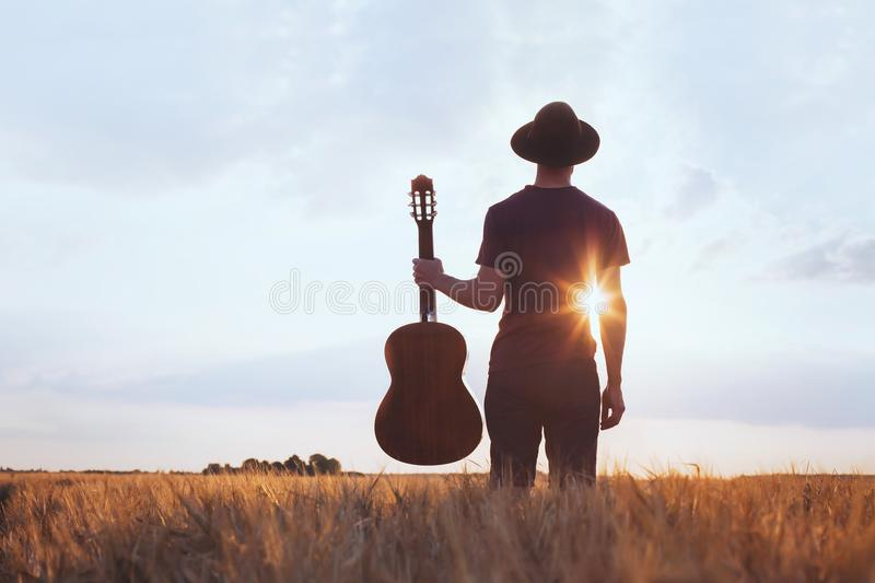 Music festival background, silhouette of musician artist with acoustic guitar. At sunset field royalty free stock photos