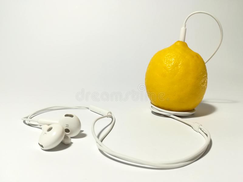 Music is food for your soul. Studio shot of headphones wrapped around a lemon on white background stock photography