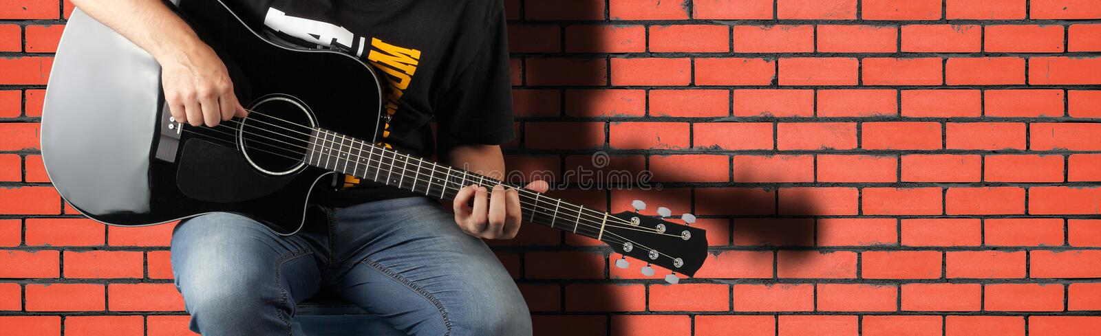 Music - Fragment man play a black acoustic guitar stock photo