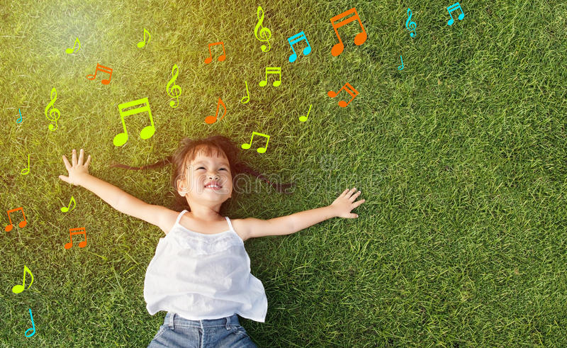 Music girl. Asian little girl smile and lay on grass with music note background royalty free stock image