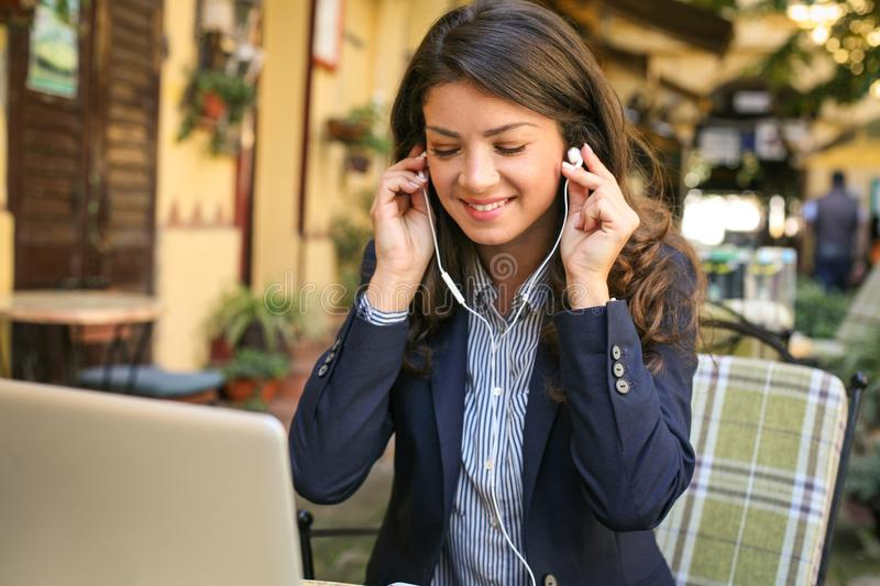 Music is good for business. Smiling happy woman listening music stock photo