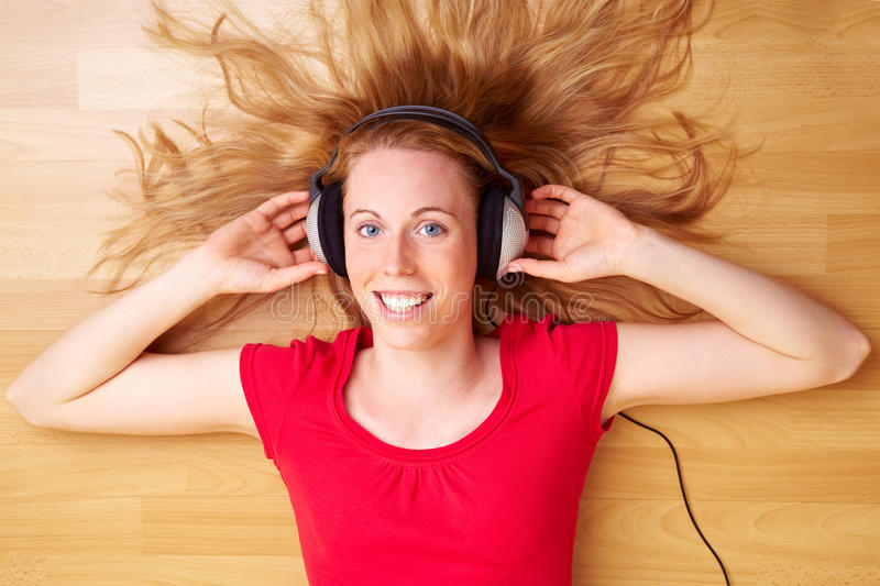Music on the ground. Happy woman with headphones listening to music stock photos