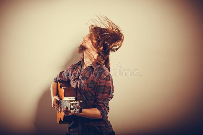 Enthusiast playing the instrument. Music hobby passion concept. Enthusiast playing the instrument. Musician is giving the performance with his guitar royalty free stock photos