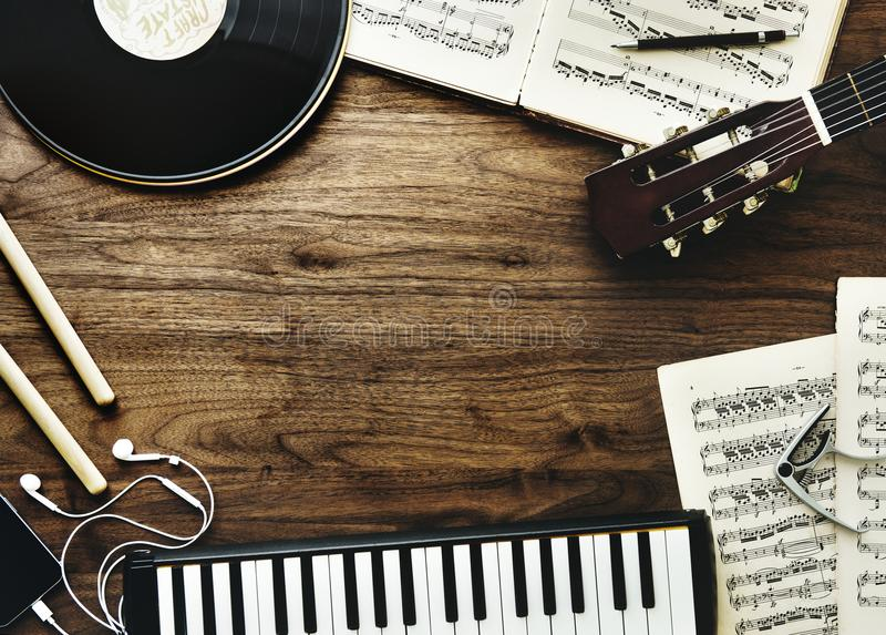 Music instruments and earphones on wooden table stock photos