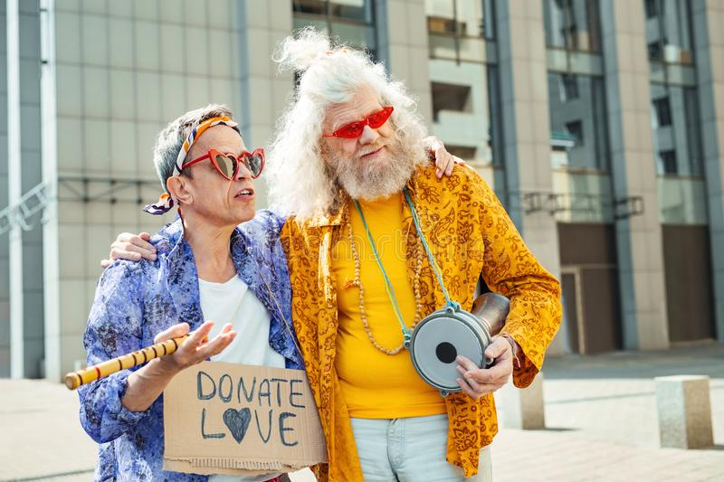 Elderly hippies wearing bright floral shirts laying music instruments royalty free stock image