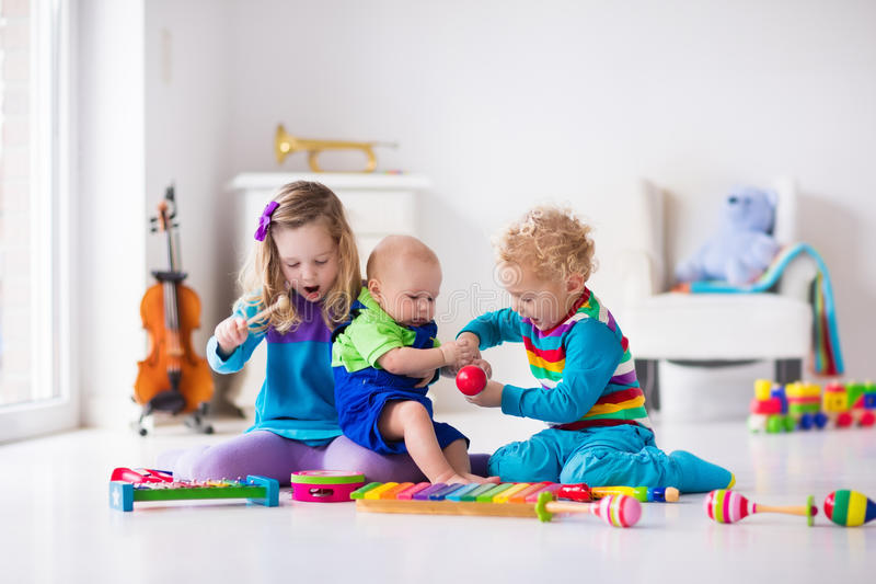 Music for kids, children with instruments. Children with music instruments. Musical education for kids. Colorful wooden art toys. Little girl and boy play music royalty free stock photography