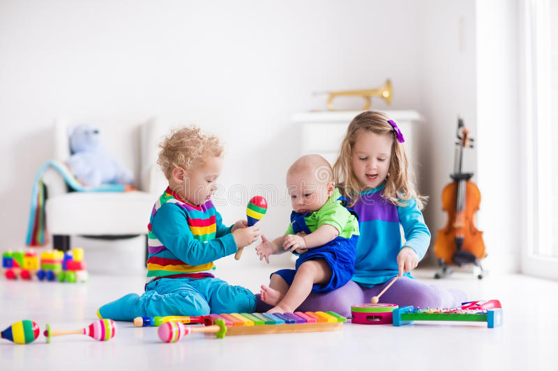 Music for kids, children with instruments. Children with music instruments. Musical education for kids. Colorful wooden art toys. Little girl and boy play music stock photography