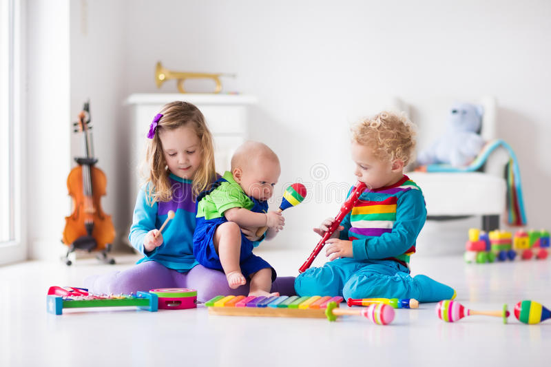 Music for kids, children with instruments. Children with music instruments. Musical education for kids. Colorful wooden art toys. Little girl and boy play music royalty free stock image